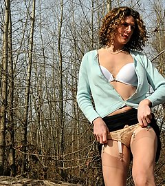 Seductive transwoman in stockings and sheer panties outside by a river.