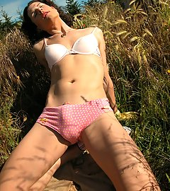 Delia outside in pink bra & panties under gardening clothes.